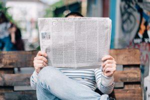 Zdjęcie mężczyzny z gazeta ilustrujące relacje z mediami organizacji pozarządowych NGO